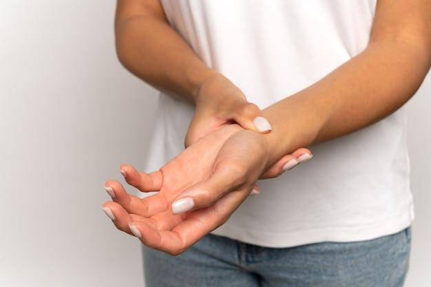 Donna che preme le dita sul polso controlla il polso femminile tocca il braccio misura il battito cardiaco o la pressione sanguigna