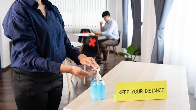 Donna che preme gel disinfettante per le mani con alcol in mano per la prevenzione delle epidemie coronavirus