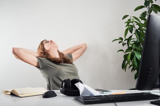 La donna procrastina il lavoro a distanza a casa sul posto di lavoro, il lavoro online e il problema dell'ufficio a casa