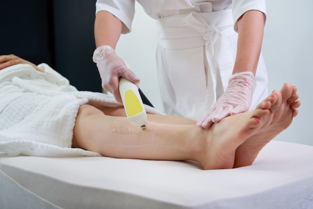 Donna in clinica di bellezza professionale durante la depilazione laser