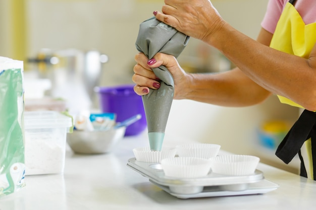 Il pasticcere professionista della donna sparge la pasta del cioccolato in teglia
