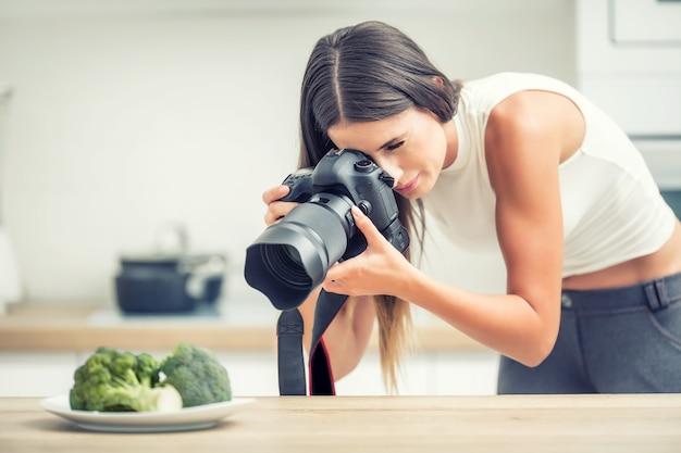 Piatto fotografico professionale della donna con i broccoli. fotografo di cibo che lavora nello studio della cucina.