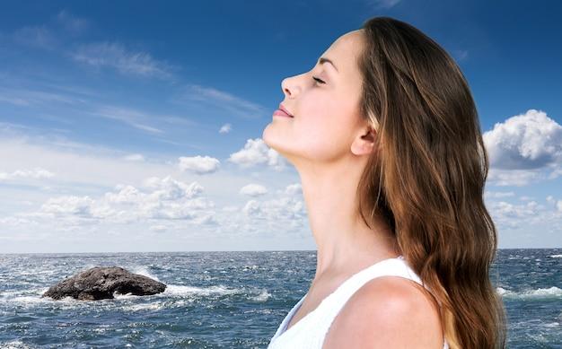 Ritratto di profilo di donna che respira aria fresca profonda sulla spiaggia con l'oceano sullo sfondo