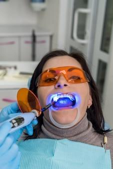 Donna con occhiali protettivi seduta sulla poltrona del dentista