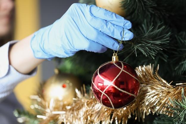 La donna in guanti protettivi appende la palla rossa di capodanno durante le vacanze dell'albero di natale nel coronavirus