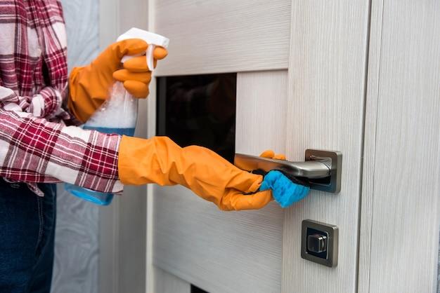 Donna in guanti protettivi in possesso di uno spray e uno straccio mentre pulisce la sua casa.