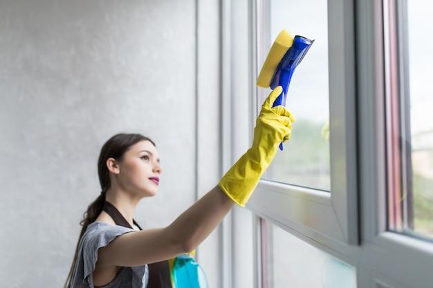 La donna in guanti protettivi sorride e pulisce la polvere usando uno spray e uno spolverino mentre pulisce la sua casa, primo piano