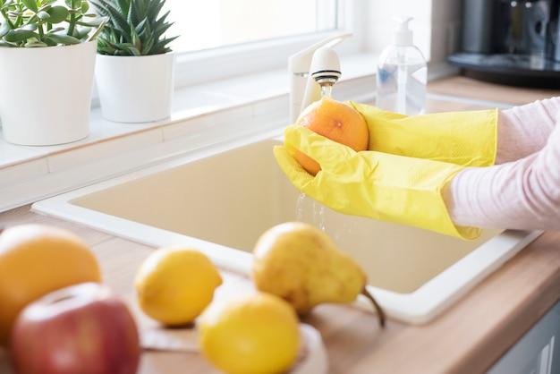 Donna in guanti protettivi che lava la frutta fresca a casa sulla cucina, detersivo in primo piano. concetto di igiene durante l'epidemia di coronavirus