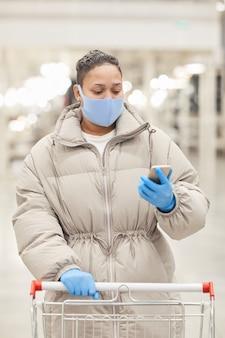 Donna in maschera protettiva leggendo la lista della spesa sul suo telefono cellulare mentre si cammina con il carrello nel supermercato