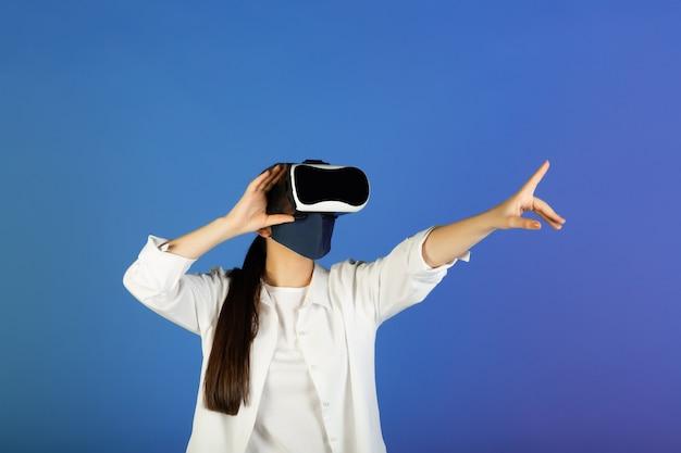 Donna in maschera protettiva con occhiali per realtà virtuale, vr, auricolare. indica con il dito indice ed esplora il mondo virtuale digitale con gli occhiali vr.
