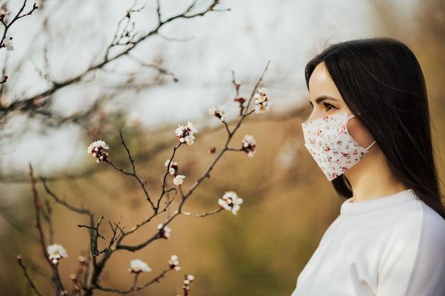 Donna in maschera protettiva medica con fiori vicino albero in fiore in primavera.