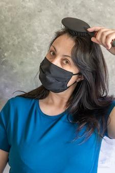Una donna in una mascherina medica protettiva comunica con la sua famiglia in cucina. tavolo grigio posteriore. lavoro a distanza.