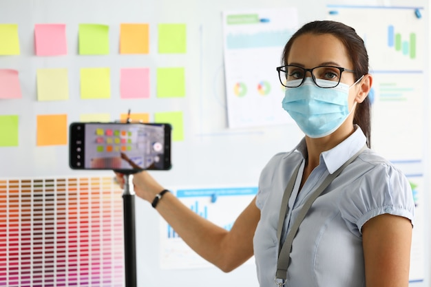 La donna nella mascherina medica protettiva tiene la conferenza di lavoro e la registra sullo smartphone.