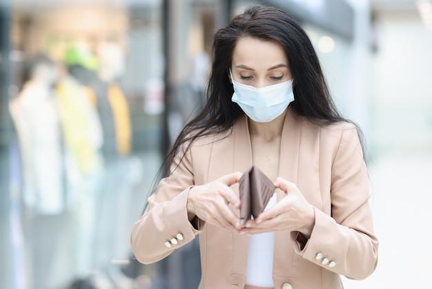 La donna in maschera medica protettiva esamina il portafoglio vuoto nel centro commerciale