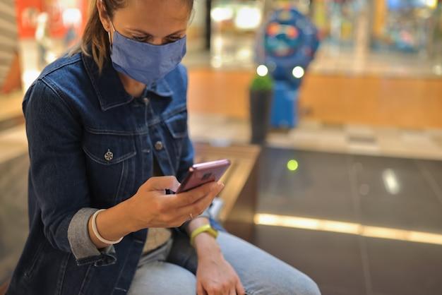 La donna nella mascherina medica protettiva si siede e tiene lo smartphone