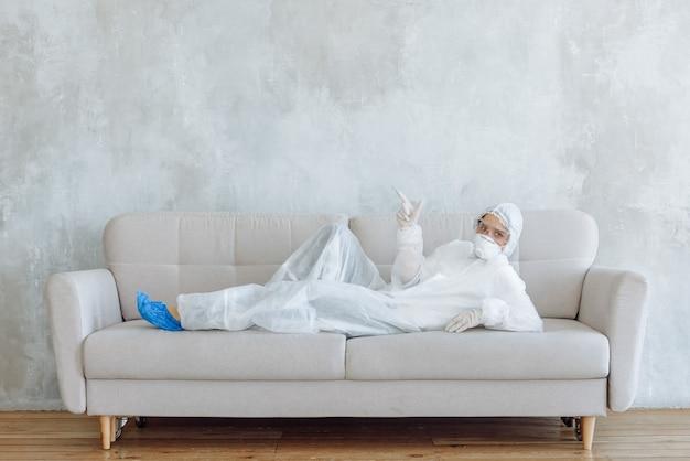 Una donna in una tuta protettiva per la disinfezione di articoli per la casa e mobili mostra un segno mentre è sdraiata su un divano.