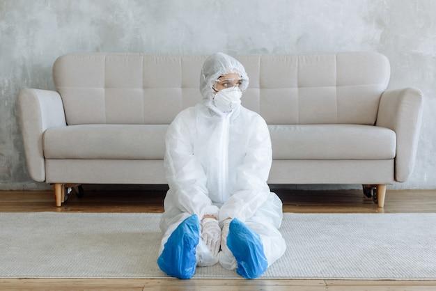 Una donna in tuta protettiva siede in una stanza della casa