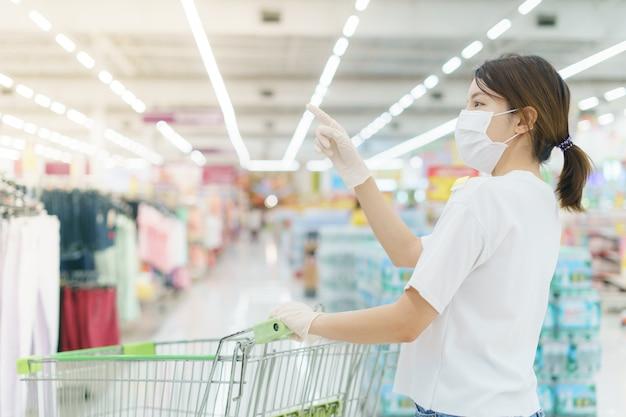La donna si protegge dalle infezioni con la mascherina chirurgica e i guanti, con il carrello per lo shopping al supermercato dopo la pandemia di coronavirus.