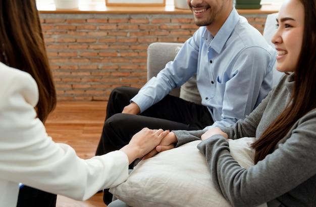 Psichiatri donna che si tengono per mano con la coppia che sorride per congratularsi con loro per la loro buona relazione dopo aver avuto problemi e ottenere consigli da uno psichiatra.