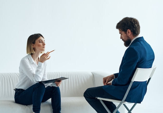 Una psicologa con documenti si siede sul divano e un uomo. foto di alta qualità