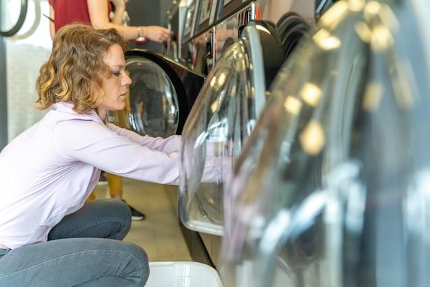 Donna che tira i vestiti dalla lavatrice automatica nella lavanderia pubblica. copia spazio