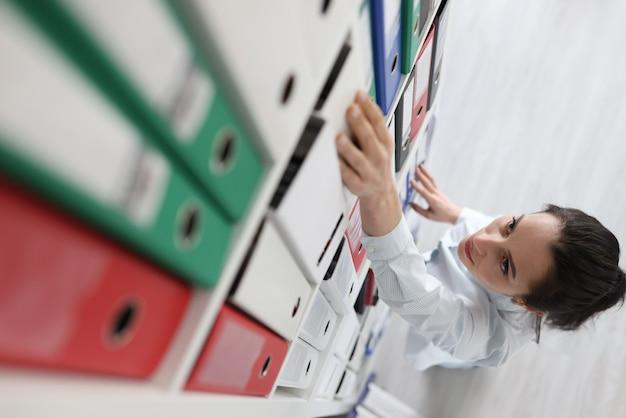 Donna che tira fuori la cartella con i documenti dallo scaffale più alto Foto Premium
