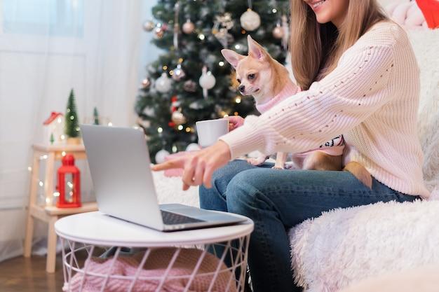 Donna e cucciolo di cane in maglione che ha una chat videochiamata sul computer portatile