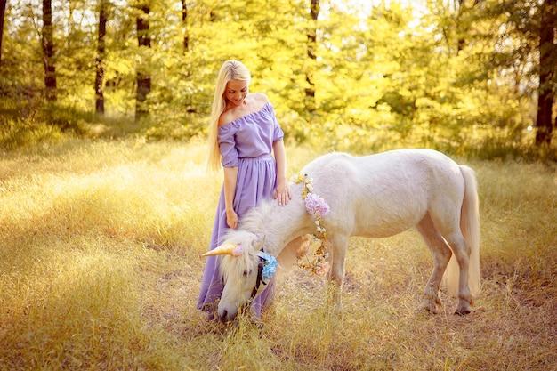 La donna in vestito viola che abbraccia i sogni del cavallo dell'unicorno bianco vieni t
