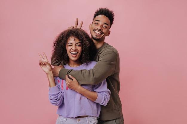 Donna in maglione viola che fa l'occhiolino. coppia che mostra segni di pace sul muro rosa