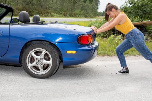 La donna spinge la macchina. era rotto sul lato