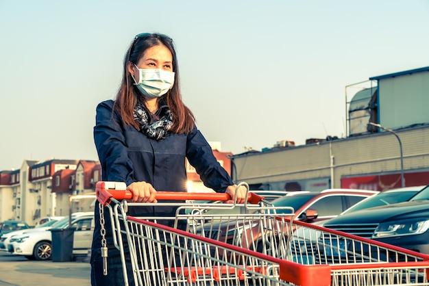 Donna che spinge il carrello della spesa nel parcheggio