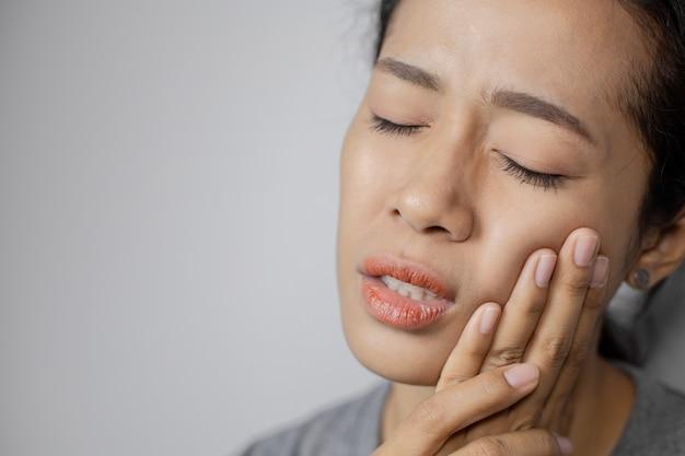 La donna si è messa la mano sulla guancia a causa del mal di denti.