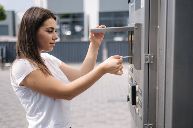 La donna ha messo la carta plactic per pagare all'aperto sull'autolavaggio self-service