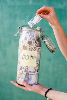 Donna che mette soldi nel barattolo con risparmi per le vacanze estive sullo sfondo verde
