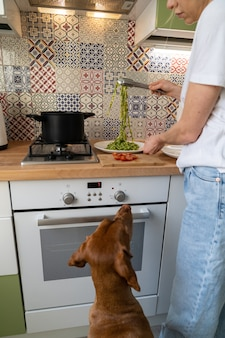 La donna mette la pasta di pesto di fettuccine dalla casseruola su un piatto, cane che implora nelle vicinanze