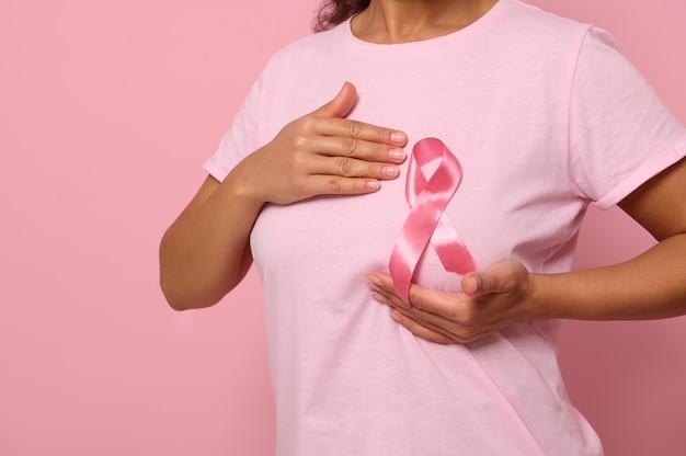 La donna mette le mani sotto il nastro rosa sulla sua maglietta rosa, sostenendo la campagna di sensibilizzazione sul cancro al seno. concetto del 1° ottobre mese rosa, assistenza sanitaria femminile, sfondo colorecd, spazio copia. avvicinamento