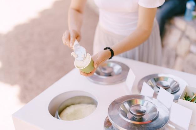 La donna mette il gelato nella tazza