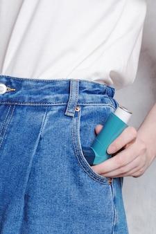La donna mette un inalatore in tasca per curare l'asma. giornata mondiale dell'asma. concetto di cura delle allergie