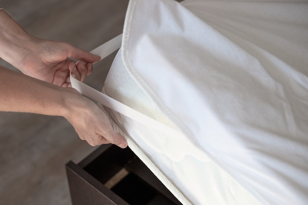Una donna mette un coprimaterasso sul letto. sonno di qualità su un letto comodo.