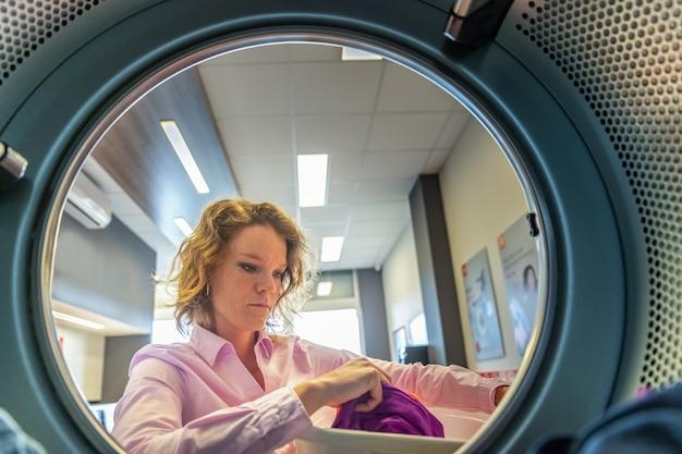 Donna che mette i vestiti in un essiccatore in una lavanderia pubblica