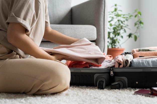 Donna che mette i vestiti in valigia per la prossima vacanza