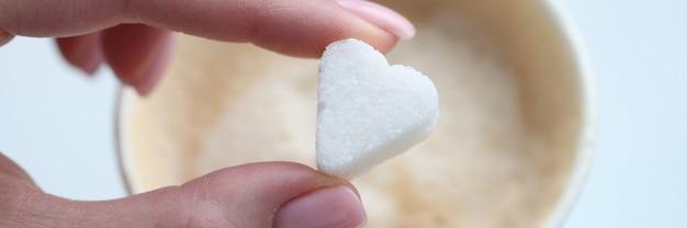 Donna che mette la zolletta di zucchero del caffè a forma di colazione del primo piano del cuore per il concetto della persona amata