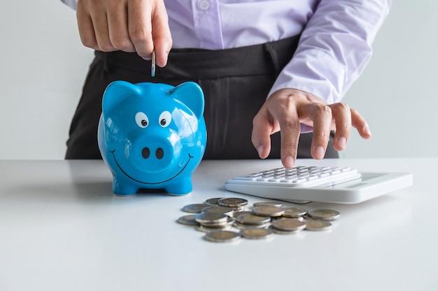 Donna che mette moneta nel salvadanaio blu per aumentare il business in crescita per trarre profitto e risparmiare con il salvadanaio, risparmiare denaro per il piano futuro e il concetto di fondo pensione.