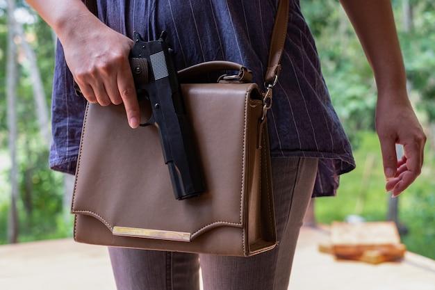 Donna che mette una pistola nella sua borsa mano delle donne che estrae una pistola dalla borsa nel parco