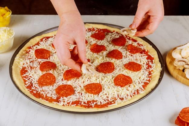 Donna che mette i funghi su pizza cruda cruda.