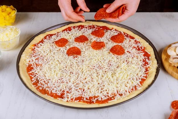 Donna che mette le salame piccante sulla pasta cruda della pizza.