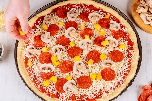 Donna che mette ananas sulla pizza cruda cruda.