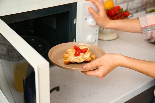 Donna che mette la piastra con il cibo nel forno a microonde