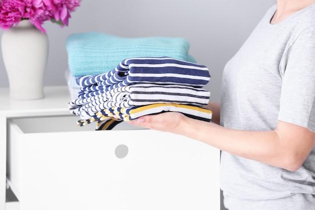 Donna che mette pila di vestiti puliti nel cassetto a casa