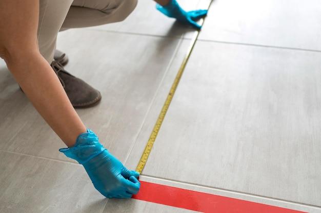 Donna che mette nastro adesivo sul pavimento per allontanamento sociale utilizzando un misuratore di nastro